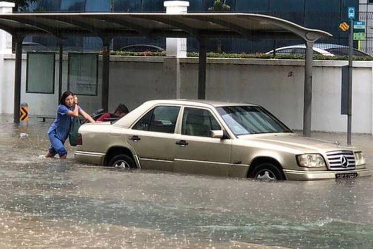 Seorang perempuan terpaksa mendorong mobilnya yang terendam banjir di kawasan Bedok Utara, Singapura, Senin (8/1/2017).
