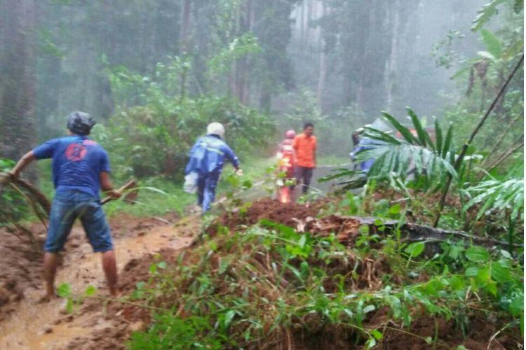 Warga dibantu TNI, Polri, dan BPBD Banjarnegara berupaya menyingkirkan material longsor yang menutup ruas jalan penghubung Kecamatan Madukara dan Pagentan, Jumat (29/9/2017).