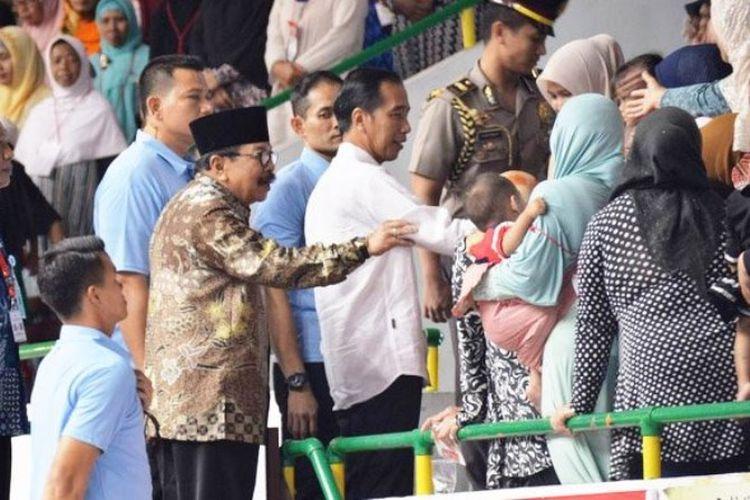 Gubernur Jawa Timur Soekarwo (berkopiah) saat mendampingi Presiden Jokowi berkunjung ke Gresik, Jawa Timur, Kamis (8/3/2018).
