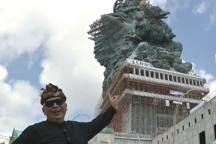 Pemrakarsa Patung Garuda Wisnu Kencana (GWK) Nyoman Nuarta berfoto dengan latar belakang pemasangan bagian Mahkota Dewa Wisnu di Ungasan, Badung, Bali, Minggu (20/5/2018). Mahkota Dewa Wisnu tersebut merupakan modul ke-529 dari total 754 modul yang terpasang di patung setinggi 121 meter yang ditargetkan selesai dibangun pada Agustus 2018.
