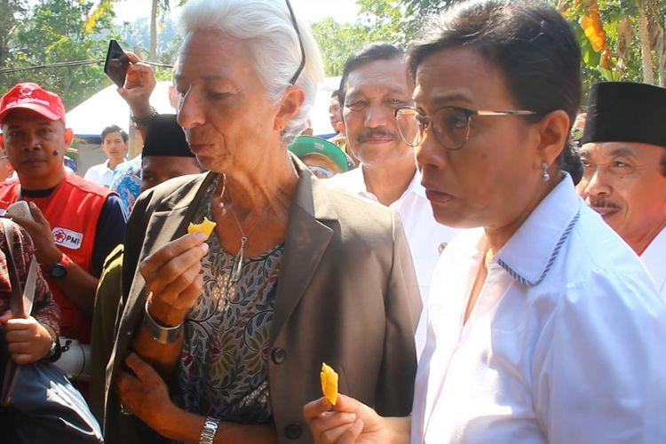 Direktur IMF Chistine Lagarde bersama Menteri Keuangan Sri Mulyani mencicipi ubi goreng  yang masih hangat, yang dijual korban gempa Lombok, di Desa Guntur Macan, Lombok Barat, Senin (8/10/2018).