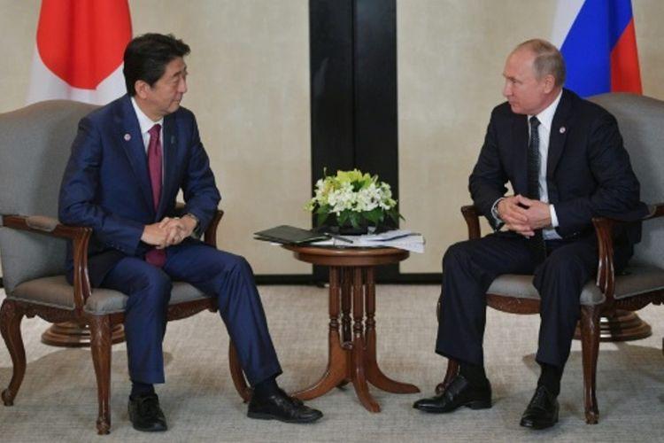 Presiden Rusia Vladimir Putin (kanan) bertemu dengan Perdana Menteri Jepang Shinzo Abe (kiri) di Singapura, Rabu (14/11/2018). (AFP/Sputnik/Alexey Druzhinin)