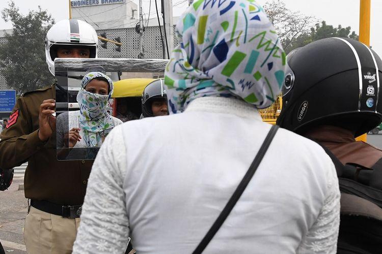 Polisi lalu lintas di Delhi, Sandeep Shahi (kiri) mengangkat cermin dan mengarahkannya ke seorang pembonceng yang tidak mengenakan helm.