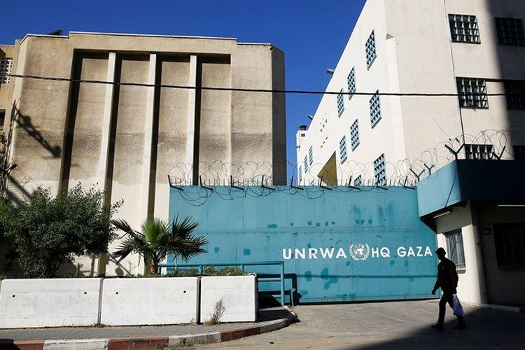 Warga Palestina melintas di depan markas besar UNRWA di Gaza.
