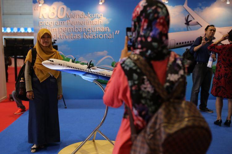 Pengunjung berfoto di dekat miniatur pesawat R80 saat pameran bidang ilmu pengetahuan, teknologi, dan inovasi, Badan Ekonomi Kreatif (Bekraf) Habibie Festival 2017 di JIEXPO, Kemayoran, Jakarta Pusat, Senin (7/8/2017). Bekraf Habibie Festival 2017 diselenggarakan mulai 7 hingga 13 Agustus dengan lebih dari 100 perusahaan dan komunitas meramaikan festival dengan beragam aktivitas yang aktual dengan perkembangan IPTEK di Indonesia.