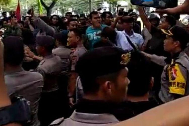Polisi sedang menenangkan massa yang menggelar aksi pro dan kontra terhadap kinerja Presiden Joko Widodo di DPRD Sumut, Kamis (20/9/2018).