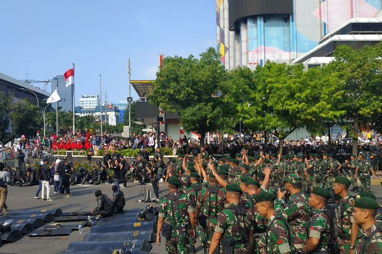 Pasukan Kostrad melambaikan tangan ke arah massa yang berunjuk rasa di depan Kantor Bawaslu di Jalan MH Thamrin di Jakarta Pusat, Rabu (22/5/2019).