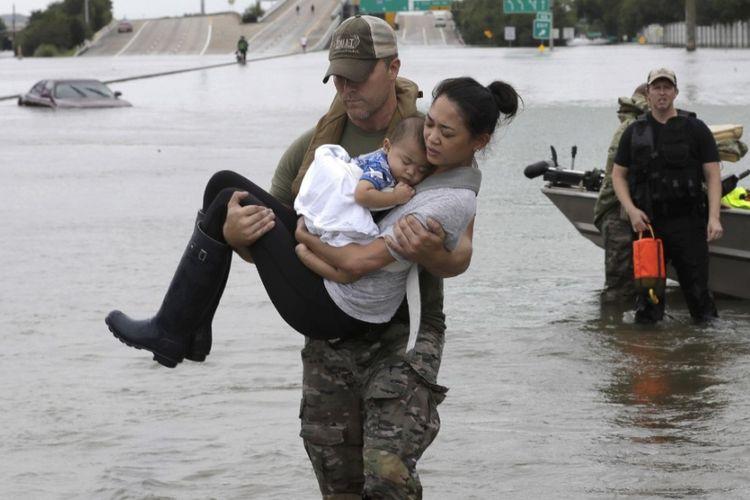 Daryl Hudeck, seorang polisi Houston, Texas, AS, menggendong Catherine Pham dan putranya, Aiden, berusia 13 bulan dalam sebuah proses evakuasi untuk menyelamatkan ibu dan anak itu dagi genangan banjir akibat badai Harvey, Minggu (27/8/2017).