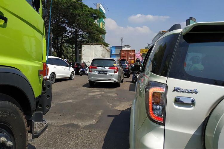 Jalanan berlubang di jalan raya menuju Bundaran Tarian Langit Kota Harapan Indah, Bekasi, Jawa Barat.