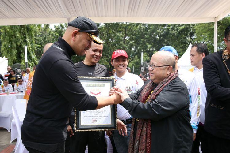 Kakorlantas Polri Irjen Refdi Andri menerima piagam Muri pecahkan rekor pembagaian 5.555 helm SNI.