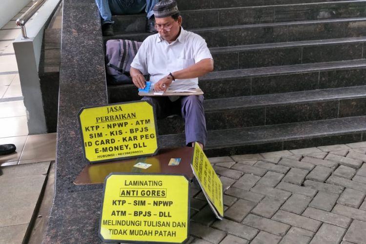 Tukang reparasi KTP, Udin (49), memperbaiki e-KTP yang rusak di area Masjid Fatahillah, Balai Kota DKI Jakarta, Rabu (6/2/2019).