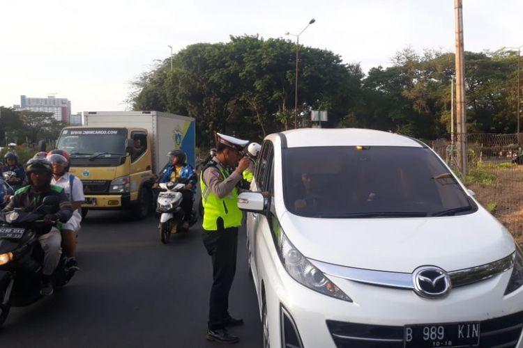 Petugas kepolisian menghentikan pengendara mobil yang melanggar sistem ganjil-genap di Jalan Benyamin Sueb, Senin (8/10/2018).
