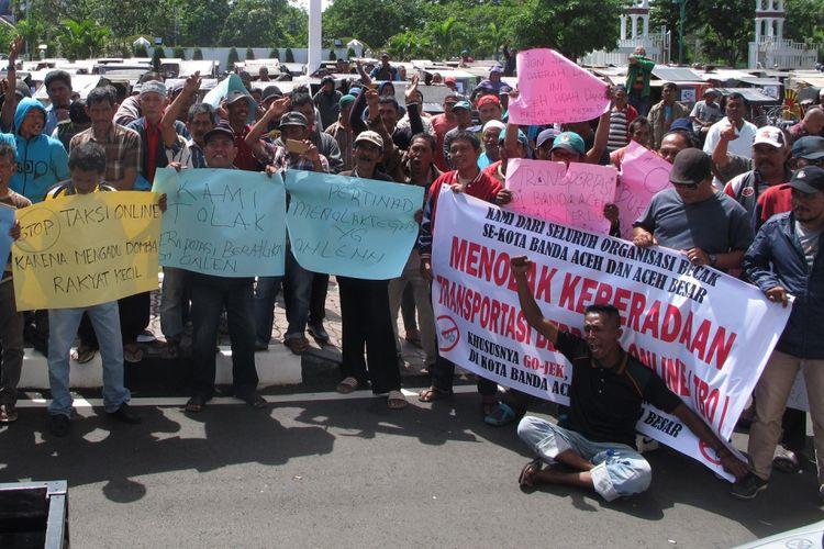 Ratusan pekerja angkutan umum di Banda Aceh melakukan aksi protes di Kantor Gubernur Aceh, Senin (16/10/2017). Mereka meminta Gubernur Aceh Irwandi Yusuf mengeluarkan perintah menghentikan aktiVitas angkutan umum berbasis online karena menurunkan pendapatan para sopir angkutan umum lainnya.