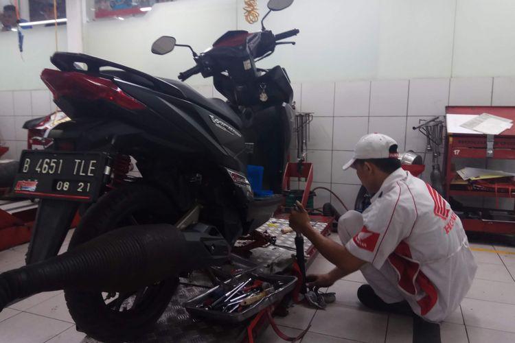 Teknisi di Bengkel Astra Motor Center Jakarta yang ada di bilangan Dewi Sartika, Jakarta Timur, tengah mengecek kondisi skutik milik pelanggan, Selasa (2/1/2018).