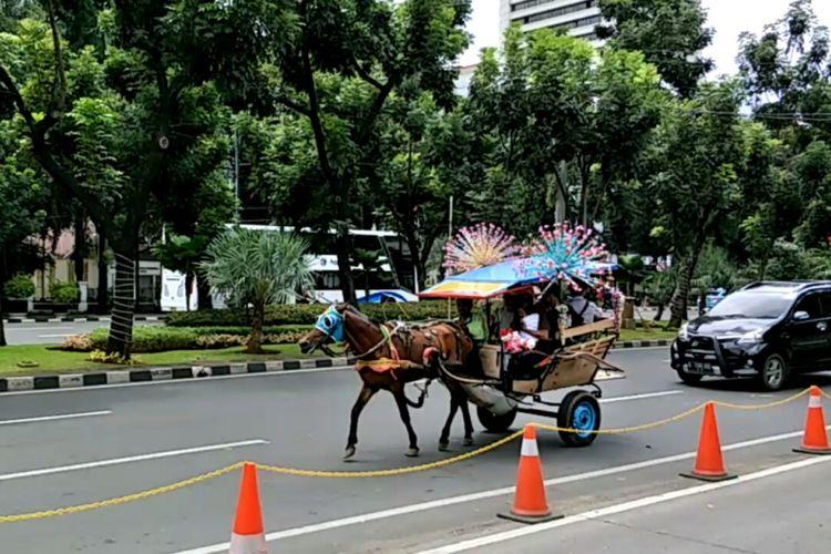 Delman hias membawa pengunjung berkeliling Monas melintas di Jalan Medan Merdeka Selatan, Selasa (26/12/2017).