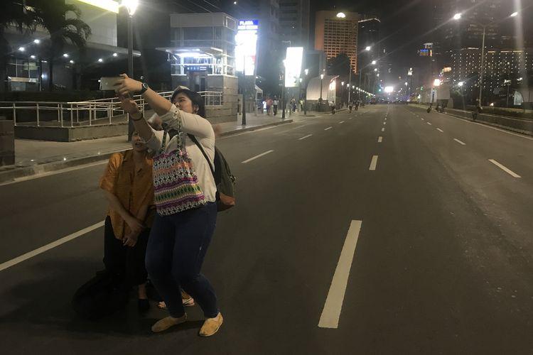 Sepulang kerja, warga yang bekerja di perkantoran di Jalan MH Thamrin hingga Bundaran HI melakukan selfie atau swafoto bersama dengan latar jalanan yang kosong dan sepi. Jalan itu belum dibuka oleh pihak kepolisian pasca-kericuhan pada 22 Mei 2019. Foto diambil Jumat (24/5/2019) malam.