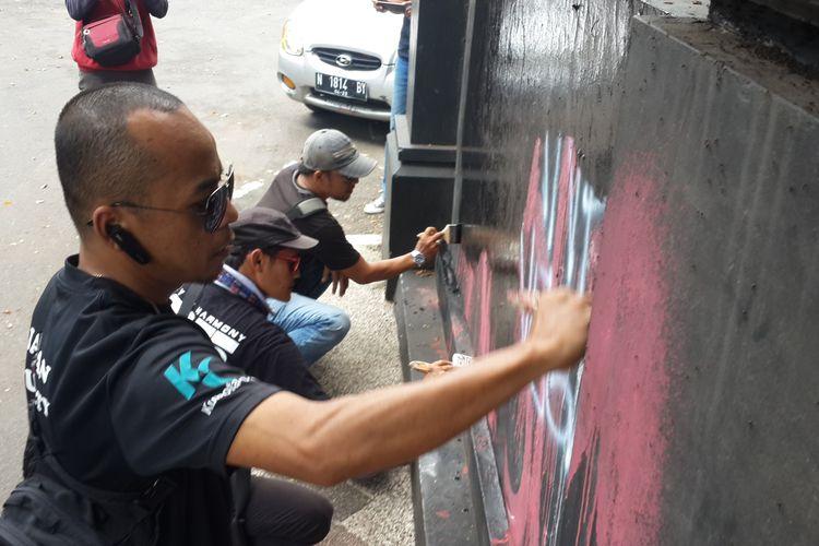 Sejumlah warga yang tergabung dalam Malang Musik Bersatu saat menghilangkan bekas vandalisme oleh sekolompok massa berpakaian hitam di Jembatan Majapahit, Kota Malang, Kamis (2/5/2019)