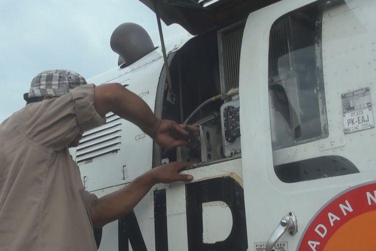 Seorang teknisi tengah memperbaiki mesin helikopter yang diduga mengalami kerusakan setelah mendarat darurat di lokasi jalan tol yang akan ditimbun. Setelah diperbaiki selama 45 menit helikopter itu terbang kembali.