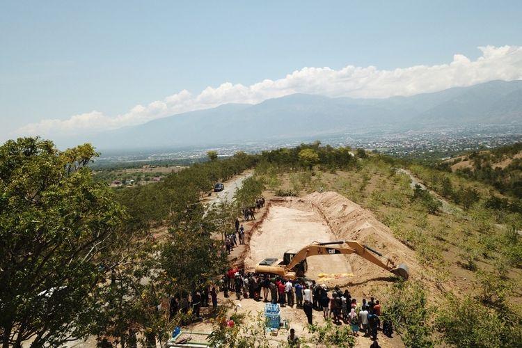 Suasana prosesi pemakaman massal korban gempa tsunami palu di Poboya, Mantikulore, Palu, Senin (1/10). Sebanyak 18 jenazah dimakamkan secara bersamaan, dan dilakukan secara bertahap.