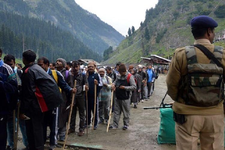 Seorang tentara berdiri mengamankan para peziarah yang berbaris menuju sebuah kuil gua di Kashmir bersamaan dengan perayaan tahunan Amarnath Yatra, Kashmir, India.