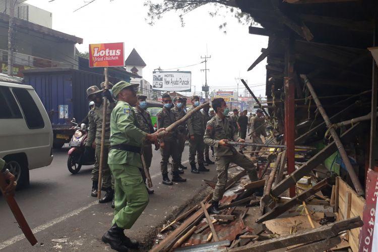 Sejumlah petugas Satpol PP Kabupaten Bogor merobohkan salah satu lapak PKL di Jalan Raya Puncak, Selasa (5/9/2017).
