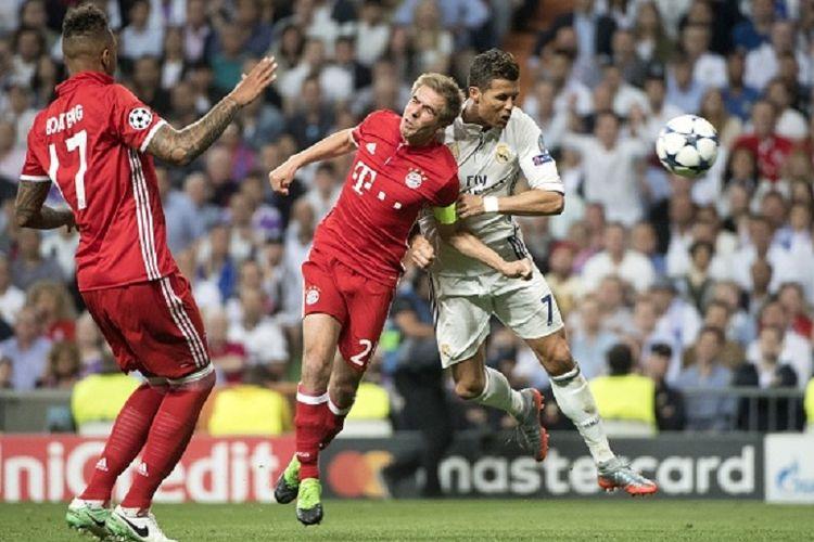 Cristiano Ronaldo mengungguli Philipp Lahm dalam menyundul bola untuk menaklukkan gawang Manuel Neur pada pertandingan perempat final Liga Champions antara Real Madrid dan Bayern Muenchen di Stadion Santiago Bernabeu, Rabu (18/4/2017).
