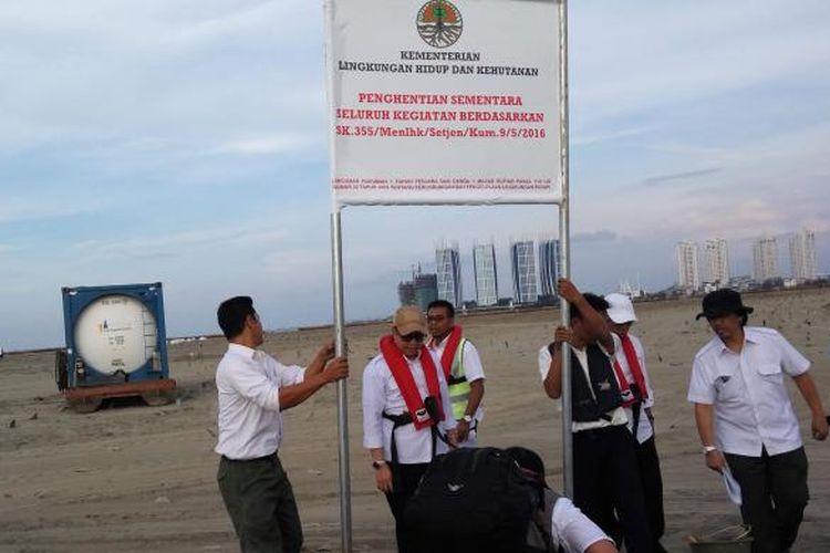 Sejumlah petugas dari Kementerian Lingkungan Hidup dan Kehutanan saat memasang plang penghentian proyek reklamasi di Pulau G pada Rabu (11/5/2016).