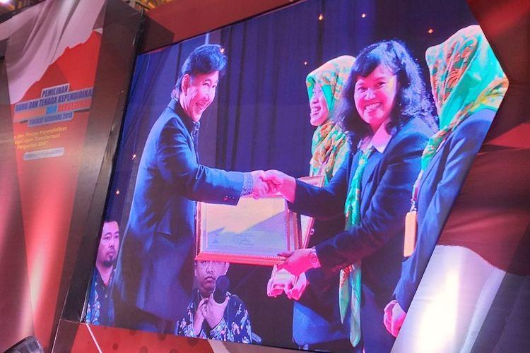 Kepala Sekolah TK Kristen Penabur, Sri Lestari, menerima penghargaan dari anggota DPR RI, Guruh Soekarno Putra, pada Malam Penganugerahan Guru dan Tenaga Kependidikan Berprestasi dan Berdedikasi di Grand Sahid Jaya Hotel, Jumat (16/8/2019).