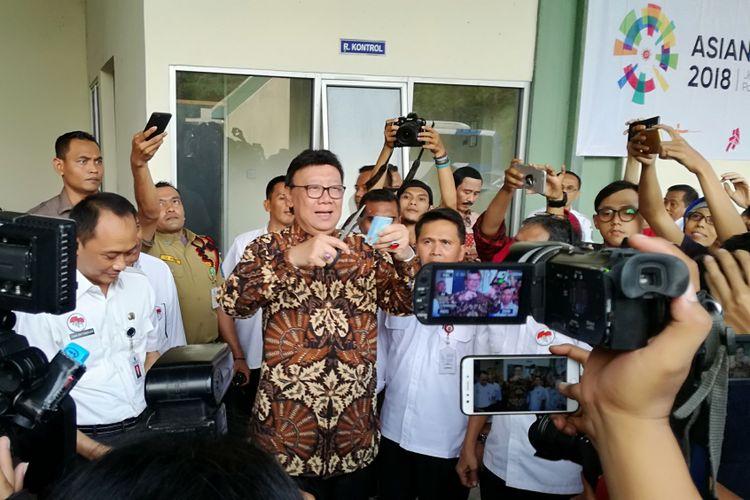 Menteri Dalam Negeri Tjahjo Kumolo memotong ujung kanan atas salah satu e-KTP yang rusak di gudang penyimpanan barang inventarisasi Kemendagri, Bogor, Jawa Barat, Rabu (30/5/2018)