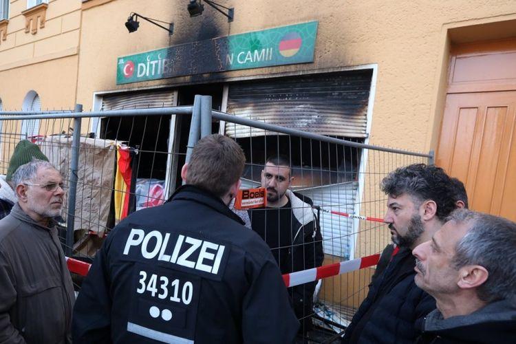 Petugas kepolisian Jerman berbicara dengan anggota masjid Koca Sinan Camii di Berlin yang menjadi sasaran bom molotov, Minggu (11/3/2018).