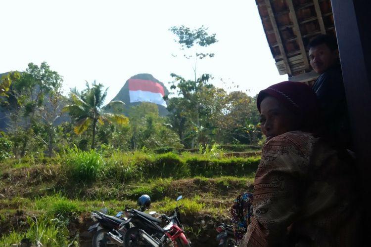 Seorang warga menyaksikan bendera raksasa di Puncak Gunung Buchu, Sekitar Gunung Api Purba Nglanggeran, Patuk, Gunungkidul, DI Yogyakarta, Senin (13/8/2018).