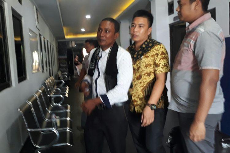 Kakak tersangka pembunuh pegawai BNN, MT (baju putih) saat mendatangi Polres Bogor untuk menjalani pemeriksaan, Jumat (8/9/2017).
