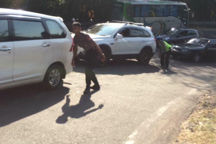 Polisi Ganjal Ban Bertugas di Tanjakan Slumprit, Patuk, Gunungkidul, membantu Kendaraan Yang terjebak Kemacetan arah Gunungkidul