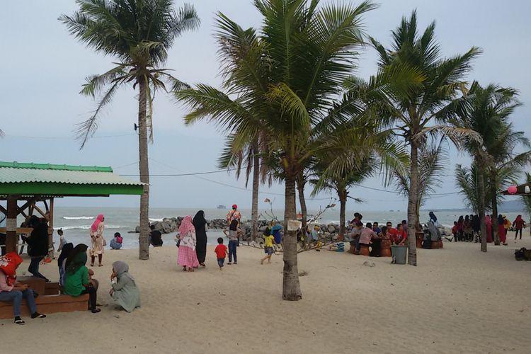 Pengunjung Pantai Batu Bedaun dengan pemandangan laut lepas bisa melihat kapal keruk timah dari lepas pantai.
