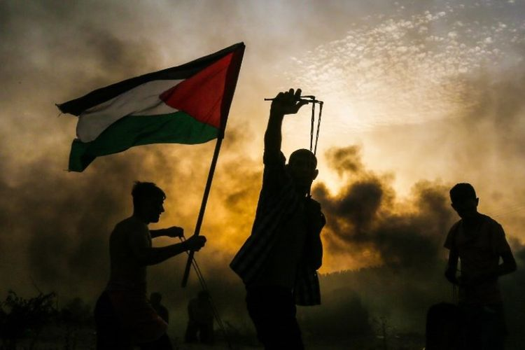 Seorang pengunjuk rasa Palestina memegang bendera saat pengunjuk rasa lainnya melemparkan batu ke arah pasukan Israel selama demonstrasi di pantai dekat perbatasan Israel, di Jalur Gaza utara, pada Senin (22/10/2018). (AFP/Mahmud Hams)