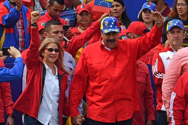 Presiden Venezuela Nicolas Maduro (tengah) didampingi istrinya, Cilia Flores, tampil di hadapan massa pro-rezim saat aksi memperingati 20 tahun revolusi di Caracas, Sabtu (2/2/2019).
