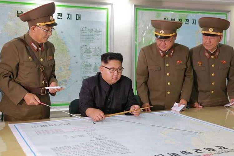 Kim Jong Un menginspeksi rencana penembakan atau serangan rudal balistik Korut ke Guam, wilayah AS di Pasifik, Senin (14/8/2017). Bersama dengan para perwira tinggi militernya, Kim Jong Un memeriksa jarak antara Korut dan Guam, serta jalur yang dilintasi rudal. Namun, akhirnya ia menunda rencana serangan rudal ke Guam tersebut.