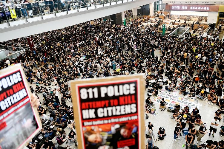 Massa pengunjuk rasa memadati aula kedatangan di Bandara Internasional Hong Kong, Senin (12/8/2019). Pengunjuk rasa yang mencapai lebih dari 5.000 orang memaksa dihentikannya operasional bandara.