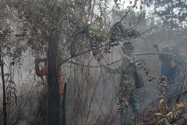 Petugas TNI dan Manggala Agni memadamkan sisa api karhutla di Kelurahan Air Hitam, Kecamatan Payung Sekaki, Pekanbaru, Riau, Minggu (21/7/2019).