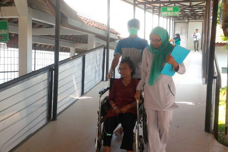 Pasien Nining Sunarsih (duduk di kursi roda) didampingi dua perawat saat dipindah ruangan di RSUD R Syamsudin,Kota Sukabumi, Jawa Barat, Rabu (4/7/2018).(KOMPAS.com/BUDIYANTO)