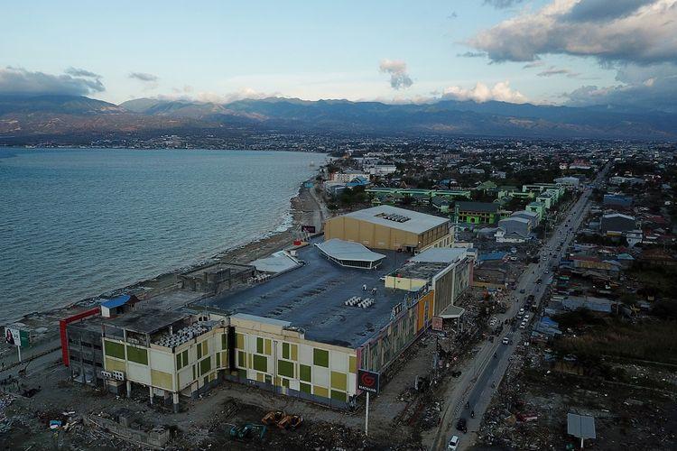 Pengendara melintasi kawasan perbelanjaan dan pertokoan yang rusak akibat tsunami pascagempa di Palu, Sulawesi Tengah, Senin (8/10). Pemerintah mulai membuka akses jalan raya dan membersihkan puing bangunan untuk memulihkan kondisi Kota Palu seusai gempa dan tsunami.