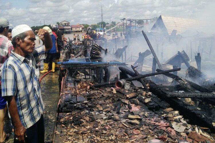 Salah satu warga sedang melihat kondisi rumahnya yang hangus terbakar di Jalan Aiptu A Wahab Lorong bersama-2 Rt 08 dan Lorong Intisari 4 Rt 11 Kelurahan 15 Ulu Kecamatan Seberang Ulu I Palembang, Sumatera Selatan, Kamis (17/5/2018).