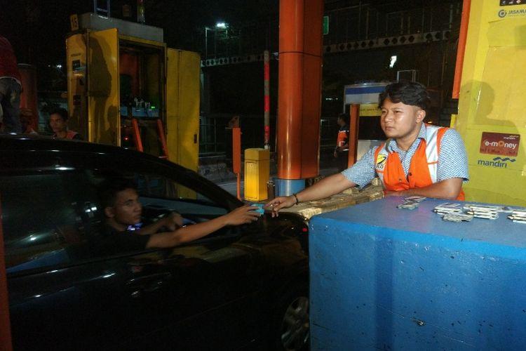 Petugas memberikan kartu tol kepada pengendara di Gerbang Tol (GT) Cibubur Ruas Tol Jagorawi sebelum GT ini dinonaktifkan dalam rangka integrasi jalan tol, Jumat (8/9/2017) pukul 00.00 WIB.