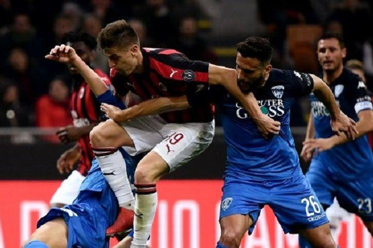 Striker AC Milan, Krzysztof Piatek (kaus merah-hitam) berebut bola dengan bek Empoli Matias Silvestre (kanan) dalam pertandingan Serie A antara AC Milan vs Empoli di Stadion San Siro, Jumat (22/2/2019).