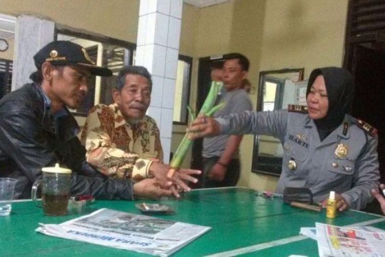 Kapolsek Bulakamba, AKP Harti (kanan) mengobati luka lecet yang dialami seorang kakek asal Cirebon yang tersesat di Bulakamba, Brebes, Jawa Tengah.