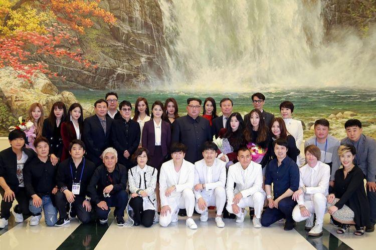 Dalam foto yang dirilis KCNA, terlihat Pemimpin Korea Utara Kim Jong Un berfoto dengan delegasi dari girlband Korea Selatan Red Velvet (1/4/2018). Konser tersebut diadakan jelang pertemuan Konferensi Antar-Korea yang bakal berlangsung pada 27 April mendatang.