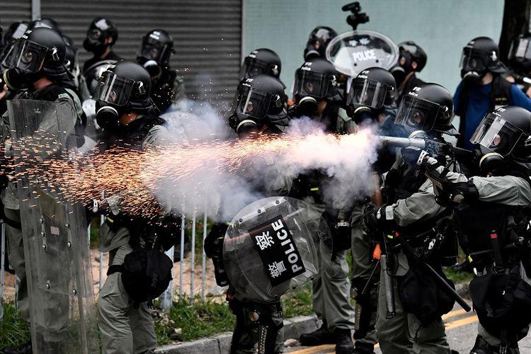 Petugas polisi anti-huru hara menembakkan gas air mata ke arah massa pengunjuk rasa dalam aksi protes di Yuen Long, Hong Kong, Sabtu (27/7/2019).