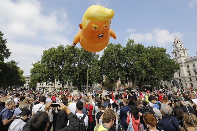 Warga London beserta para aktivis mengabadikan balon bayi Trump raksasa saat diterbangkan di tengah aksi demonstrasi memprotes kunjungan Presiden AS ke Inggris, Jumat (13/7/2018).