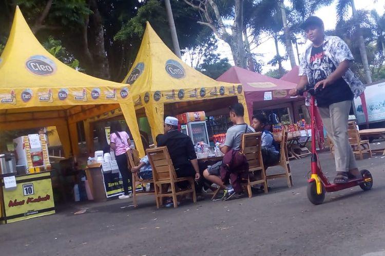 Seorang pengunjung sedang menaiki skuter elektrik yang disewakan di Kawasan Wisata Waduk Darma di Kuningan, Jawa Barat.