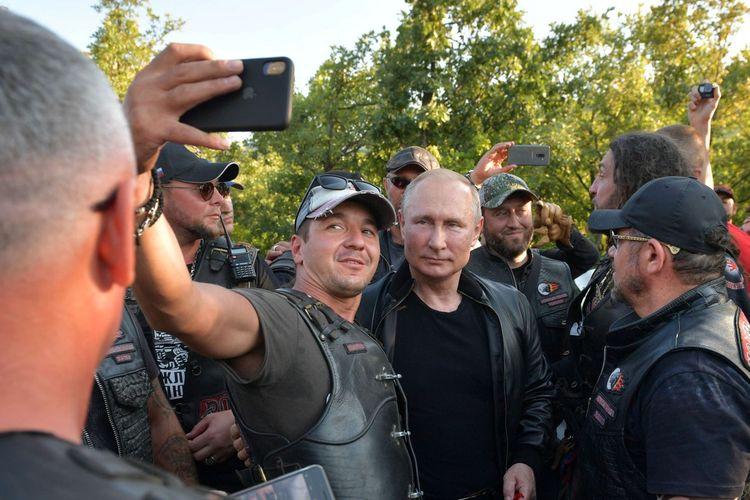 Presiden Rusia Vladimir Putin ketika selfie bersama seorang anggota geng motor Night Wolves ketika datang dalam acara hari jadi mereka di Sevastopol, Crimea. Kunjungan itu terjadi tengah aksi unjuk rasa yang menentang Putin.